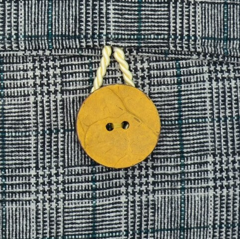 Dies ist ein Detail der Rückseite eines Kissen-Unikats von AN-NA Design, einer kleinen Kissen-Manufaktur im Bergischen Land. Der Knopf ist aus Kokos gefertigt.