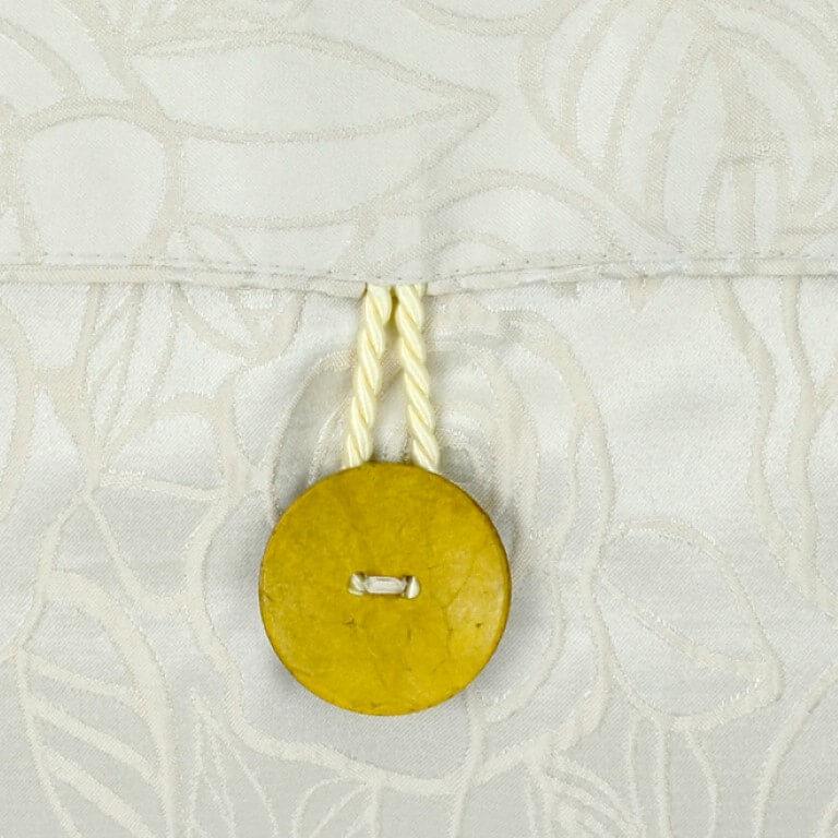 Ein farbenfrohes Kissen-Unikat von AN-NA Design in den Farben Blau, Türkis und Gelb. Dies ist die Rückseite in hellem Jacquard-Stoff mit gelben Kokos-Knöpfen.
