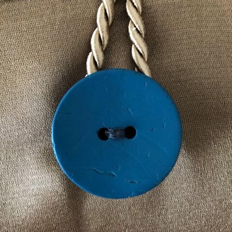 Ein Kissen als Kunst-Objekt von AN-NA Design, handbemalt und handbedruckt. Hier die Rückseite mit Kokos-Knopf